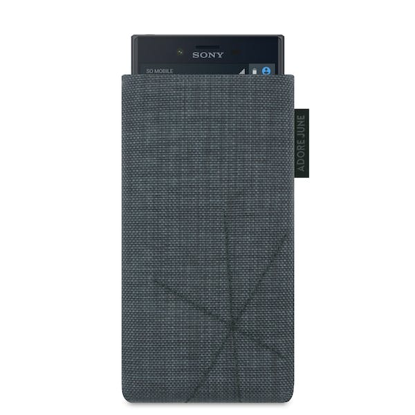 The picture shows the front of Axis Sleeve for Sony Xperia X Compact in color Dark Grey; As an illustration, it also shows what the compatible device looks like in this bag